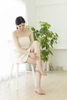 椅子に座りお肌の手入れをする若い女性