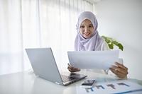 書類を見るムスリムの女性