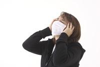マスクをして頭を押さえる女性