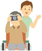写真を撮る老人男性と介護士