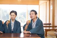 ビールで乾杯す浴衣と羽織の中高年夫婦と祖父母