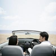 オープンカーに乗るカップルの後ろ姿