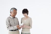 プレゼントを持つ日本人シニア夫婦 白バック