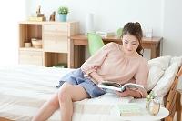 部屋で本を読む日本人女性