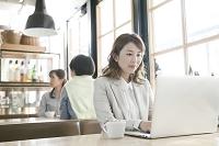 カフェでノートパソコンを使う若い女性