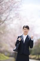 桜並木の前でガッツポーズをするフレッシャーズ