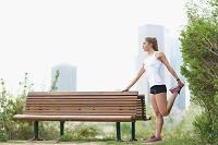 公園でストレッチする若者の女性