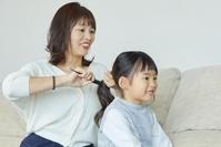母親に髪を結んでもらう女の子