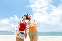 ビーチボールと浮き輪を持った笑顔の日本人女性