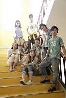 階段で微笑む8人の男女大学生