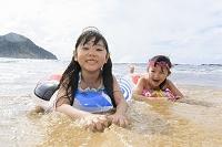 海辺で寝そべって遊ぶ日本人の女の子