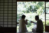 縁側で日本酒を飲むシニアカップル