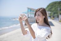 海の堤防でスマートフォンで音楽を聴き写真も撮る日本人女性