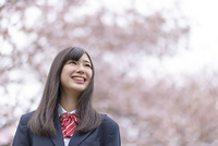 桜の前で微笑む女子学生