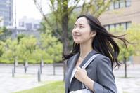 髪をなびかせ歩く日本人ビジネスウーマン