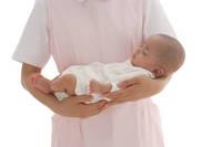 看護師に抱かれて眠る赤ちゃん
