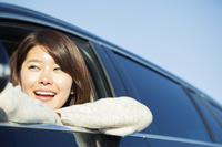 車の窓に腕をかける笑顔の20代日本人女性