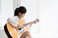 ギターを弾く笑顔の日本人女性