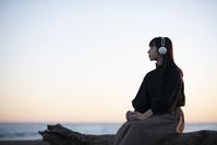 海辺で音楽を聴く日本人女性