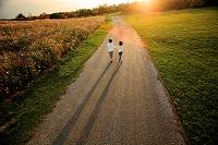 夕日に向かって道を歩く子供