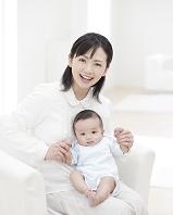 赤ちゃんを膝の上にのせてソファに座る母親