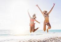 海辺でジャンプする水着の女性