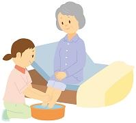 ベッドで足を洗ってもらう老人女性と介護士
