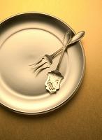 金色の皿にケーキ用スプーンとフォーク