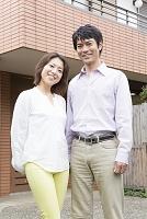 家の前で微笑むミドル夫婦