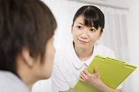 患者と話をする日本人の女性看護師