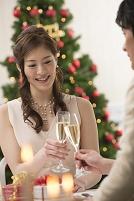 クリスマスツリーとシャンパンで乾杯するカップル