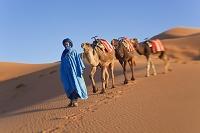 モロッコ 砂漠を歩くトゥアレグとラクダ