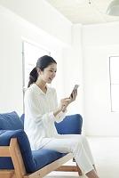 ソファーでスマートフォンを使う20代日本人女性