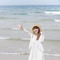 海辺で麦わら帽子をかぶった日本人女性