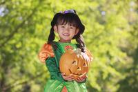ハロウィンの仮装をしてカボチャをもつ少女