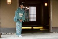 玄関で挨拶する中高年日本人女性