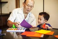 折り紙で遊ぶ祖父と孫