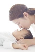 眠る赤ちゃんにキスをする母