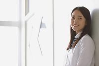 教室のドアに寄り掛かる女子高生