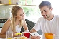 朝食を食べながらスマートフォンを見る外国人カップル