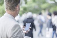 道でスマートフォンを使用する外国人男性
