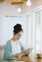 カフェでタブレットを使う日本人女性