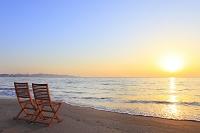 神奈川県 波打ち際の砂浜に置かれた椅子と朝日