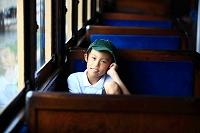 列車の座席に座る少年