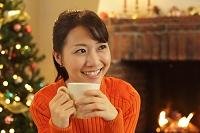 クリスマスの日に暖炉の前で寛ぐ女性