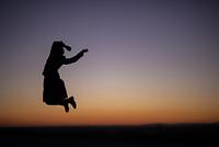 夕焼けの中でジャンプする女性のシルエット