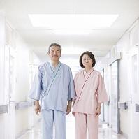 検査衣を着て廊下に立つ中高年男女
