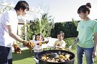 庭でバーベキューを楽しむ家族