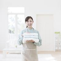 タオルを持つエプロン姿の日本人女性