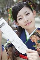 おみくじの結果を見せ微笑む振袖姿の日本人女性